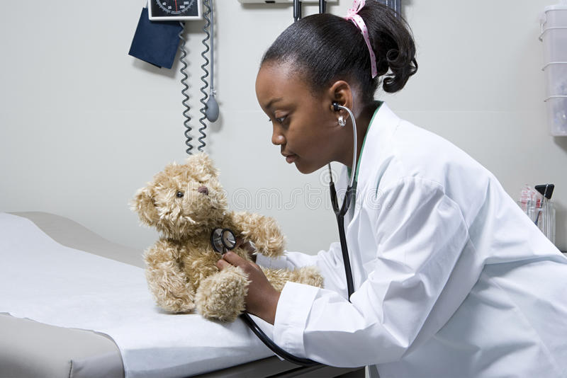 Mädchendoktor, der Stethoskop auf Teddybären verwendet lizenzfreies stockfoto