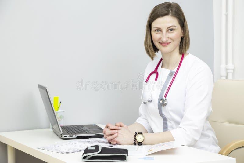 Mädchendoktor am Tisch mit einem Laptop stockfotos