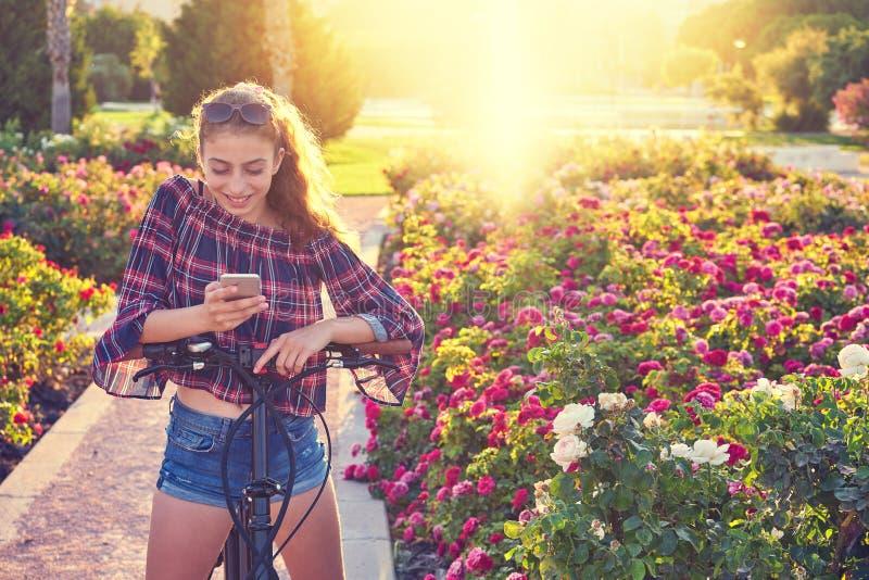 Mädchenfahrrad, das mit Smartphone im Park spielt lizenzfreies stockbild