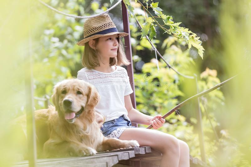 Mädchenfischen beim Sitzen mit Hund auf Pier lizenzfreie stockbilder