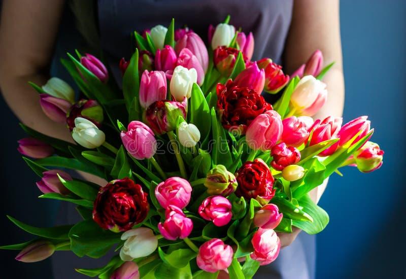 Mädchenflorist, der einen Blumenstrauß von Tulpen hält stockbild