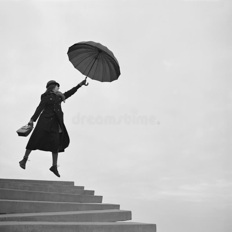 Mädchenflugwesen weg auf Regenschirm lizenzfreie stockfotografie