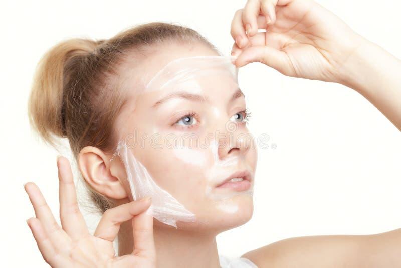 Mädchenfrau in Gesichts ziehen weg Maske ab Zutreffen des transparenten Lacks lizenzfreie stockbilder