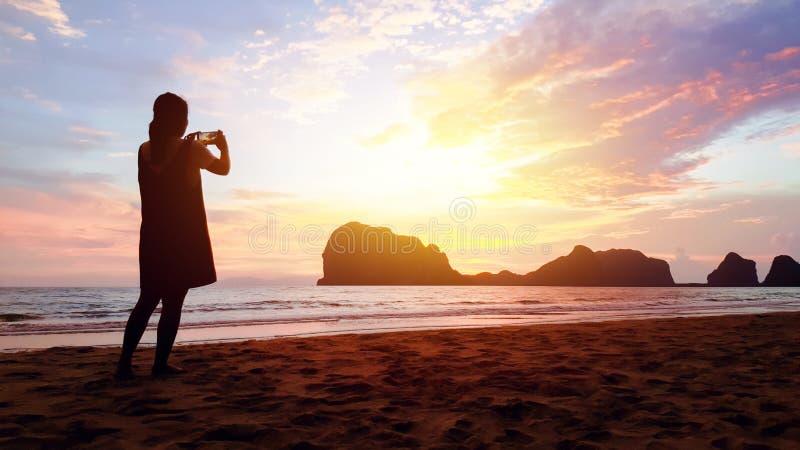 Mädchenfrauen-Gebrauchsmobile vertreten die Fotosonnenuntergangansicht von Inseln, von Bergen, von Meer, von Sand und von Himmel  stockfotografie
