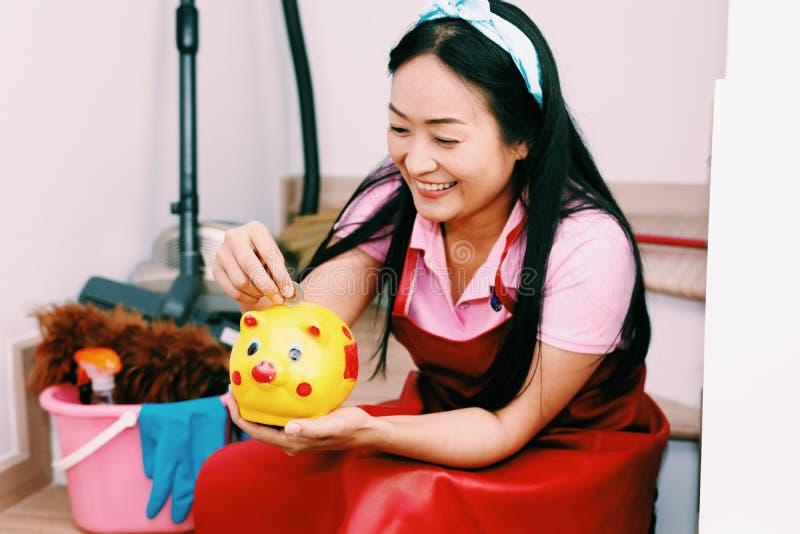 Mädchenfrauenablagerungs-Goldmünze der jungen Mischrasse asiatische in Sparschwein für das zukünftige Leben, das zu Hause auf Tre lizenzfreies stockbild