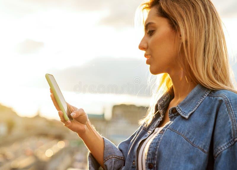 Mädchenfreiberufler, der mit Telefon bei Sonnenuntergang arbeitet stockfotografie