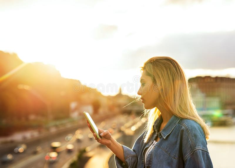 Mädchenfreiberufler, der mit Telefon bei Sonnenuntergang arbeitet lizenzfreie stockfotos