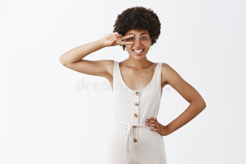 M?dchengef?hl hob empor und w?nschte Tag erhellen Portr?t der frohen sch?nen afro-amerikanischen Frau im grauen Overall stockfotografie