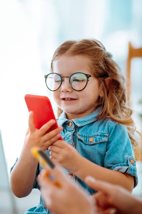 Mädchengefühl unterhalten, Spiel am Telefon spielend, das nahe Mutter sitzt lizenzfreie stockfotografie