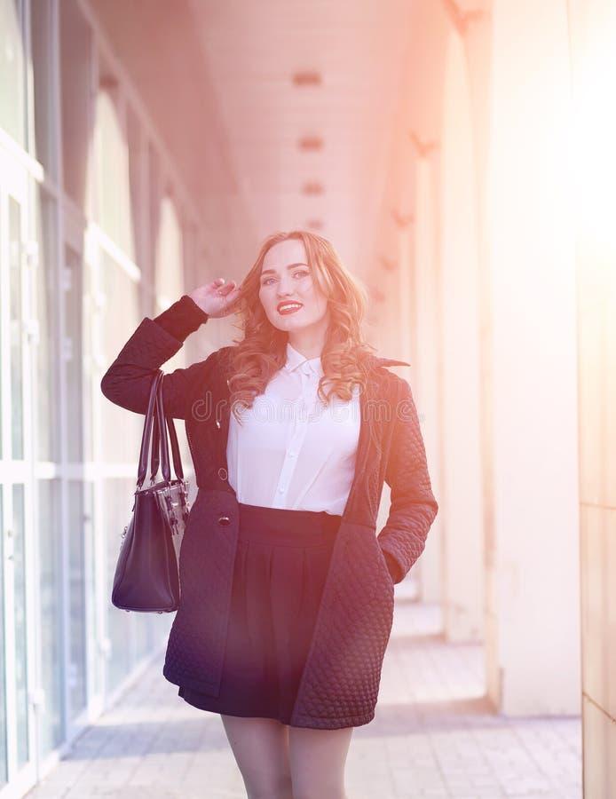 MädchenGeschäftsfrau im Frühjahr auf einem Weg in einem Mantel stockfoto