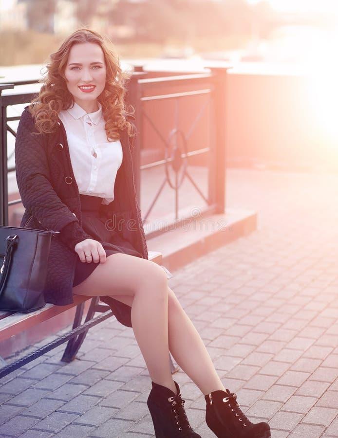 MädchenGeschäftsfrau im Frühjahr auf einem Weg in einem Mantel lizenzfreie stockfotos