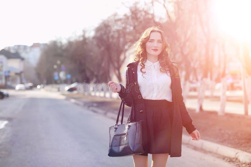 MädchenGeschäftsfrau im Frühjahr auf einem Weg in einem Mantel lizenzfreies stockbild