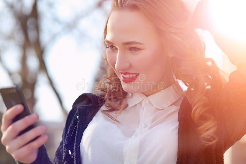 MädchenGeschäftsfrau im Frühjahr auf einem Weg in einem Mantel stockfotos