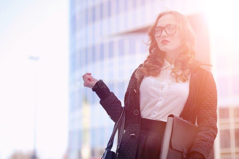 MädchenGeschäftsfrau im Frühjahr auf einem Weg in einem Mantel lizenzfreies stockfoto
