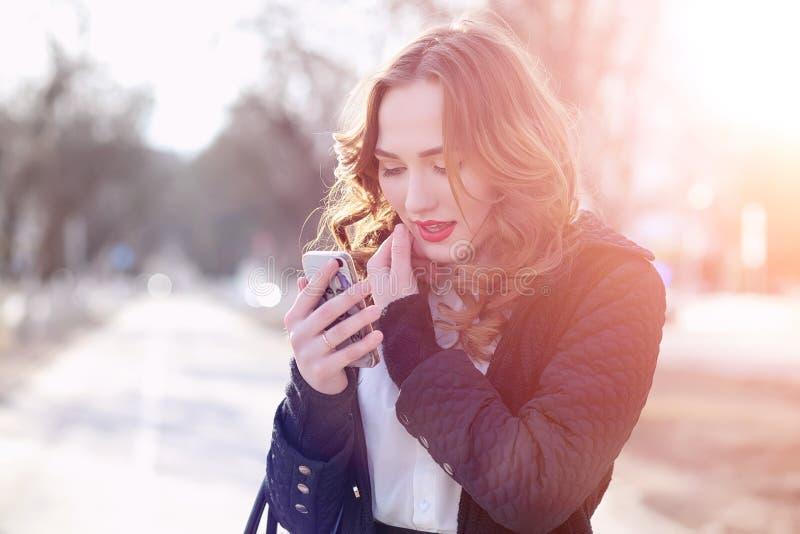 MädchenGeschäftsfrau im Frühjahr auf einem Weg in einem Mantel lizenzfreie stockfotografie