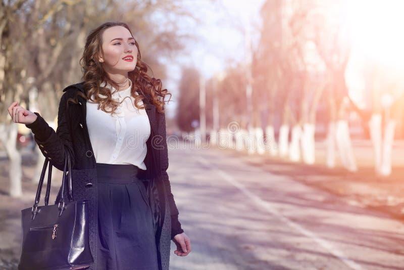 MädchenGeschäftsfrau im Frühjahr auf einem Weg in einem Mantel lizenzfreie stockbilder