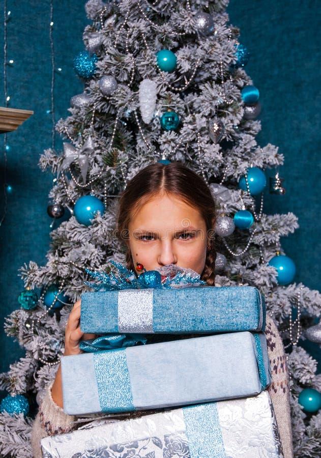 Mädchengriff Stapel der Weihnachtsgeschenkgeschenkbox auf Weihnachtsbaumhintergrund lizenzfreie stockfotografie