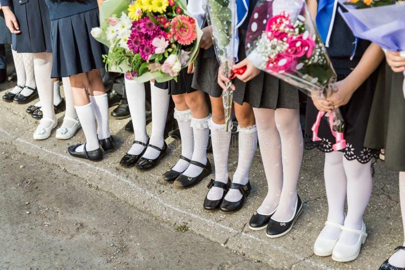 Mädchengrundschule mit Blumensträußen von Blumen in seinen Händen Schuhe auf ihrer Fuß- und weißenstrumpfhose, Socken und Strümpf stockfotografie