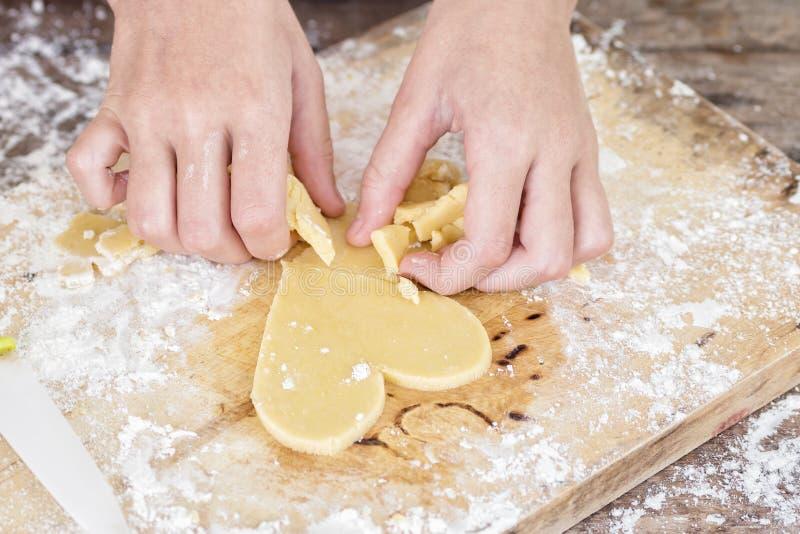 Mädchenhände, die Herz geformtes Plätzchen machen Abschluss oben stockfotografie