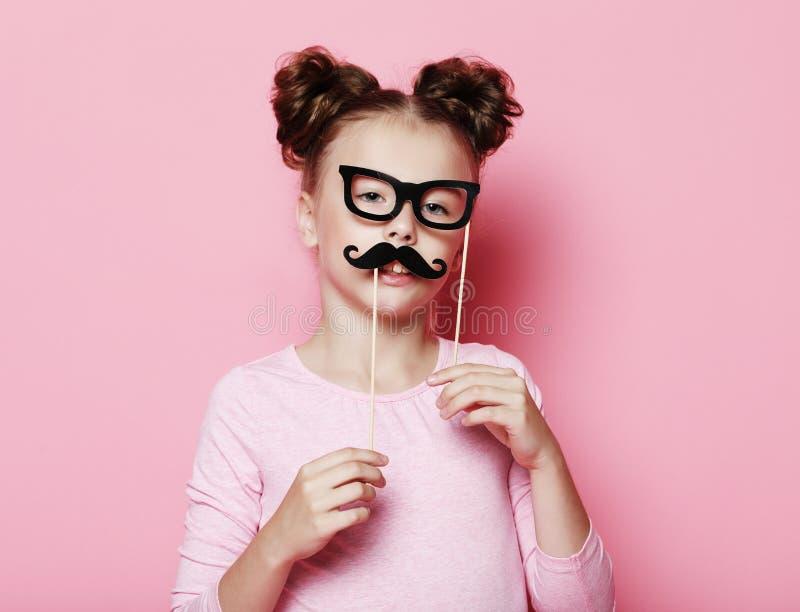 Mädchenhaltung mit Passfotoautomatstützengläsern und -schnurrbart stockbilder