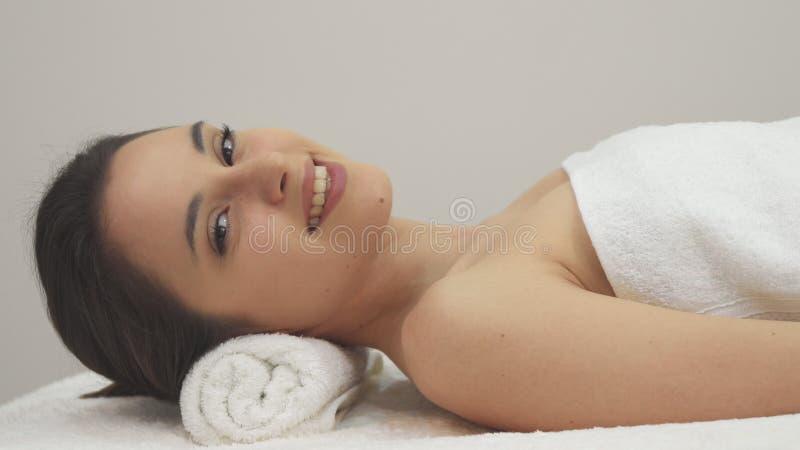 Mädchenhaltungen auf der Massagetabelle lizenzfreie stockbilder
