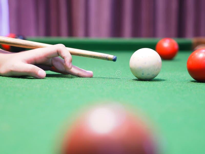 Mädchenhand auf der grünen Tabelle, die Billardkugeln spielt stockfoto