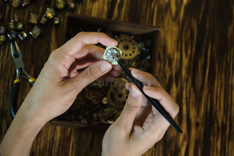Mädchenhandwerker baut Uhren ab stockfotos