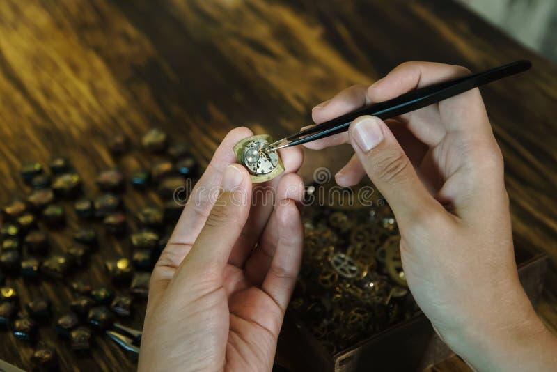 Mädchenhandwerker baut Uhren am Arbeitsplatz ab stockfotografie