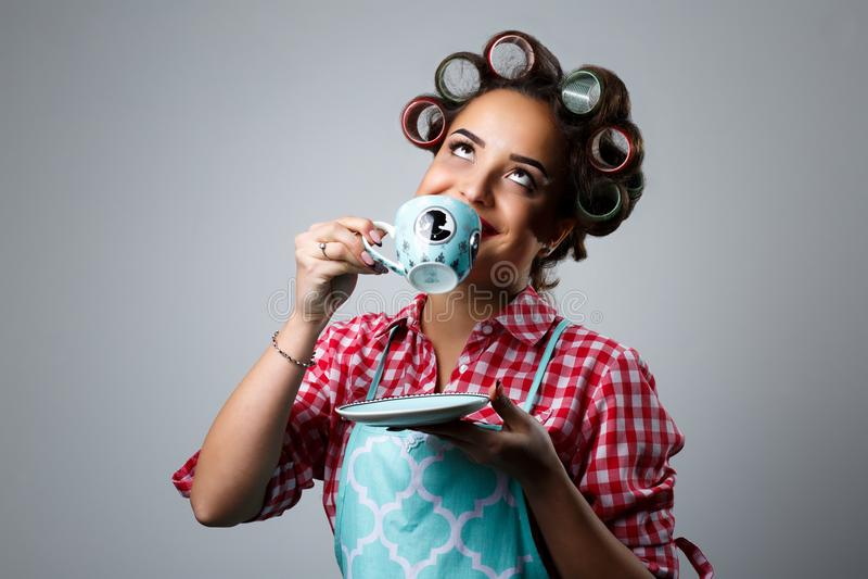 Mädchenhausfrau trinkt Tee von einer Schale lizenzfreie stockfotos