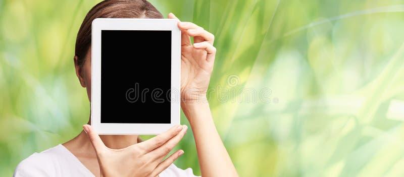 M?dchenholding-Computerauflage Schein oben am Tablettenschwarzschirm Gesicht nahe Laptop Frauenvertretungs-PC lizenzfreies stockfoto