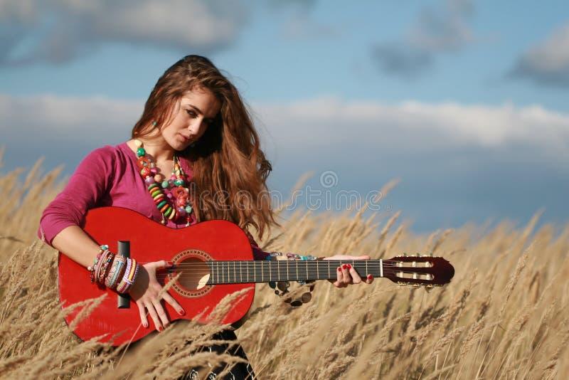 Mädchenholding, die Gitarre auf dem Gebiet spielt lizenzfreie stockfotografie
