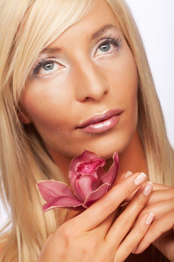 Mädchenholding-Orchideeblume stockfotografie