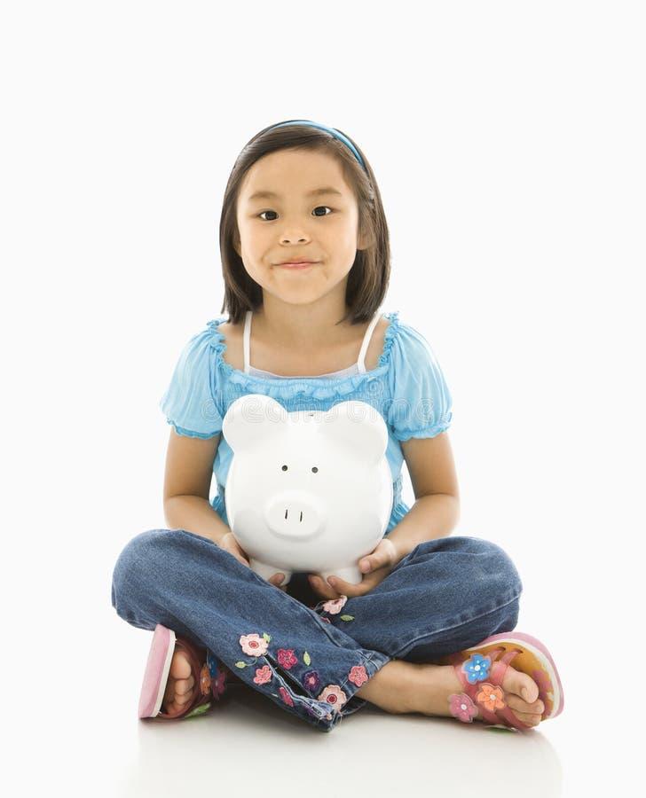 Mädchenholding piggybank. stockbild