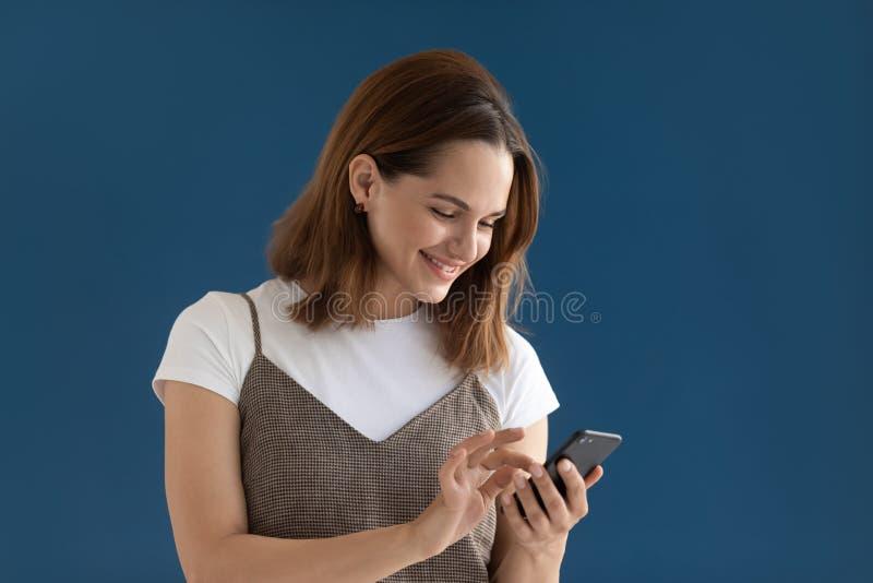 Mädchenholding Smartphone unter Verwendung der Edatierungsanwendungsatelieraufnahme lizenzfreie stockfotos