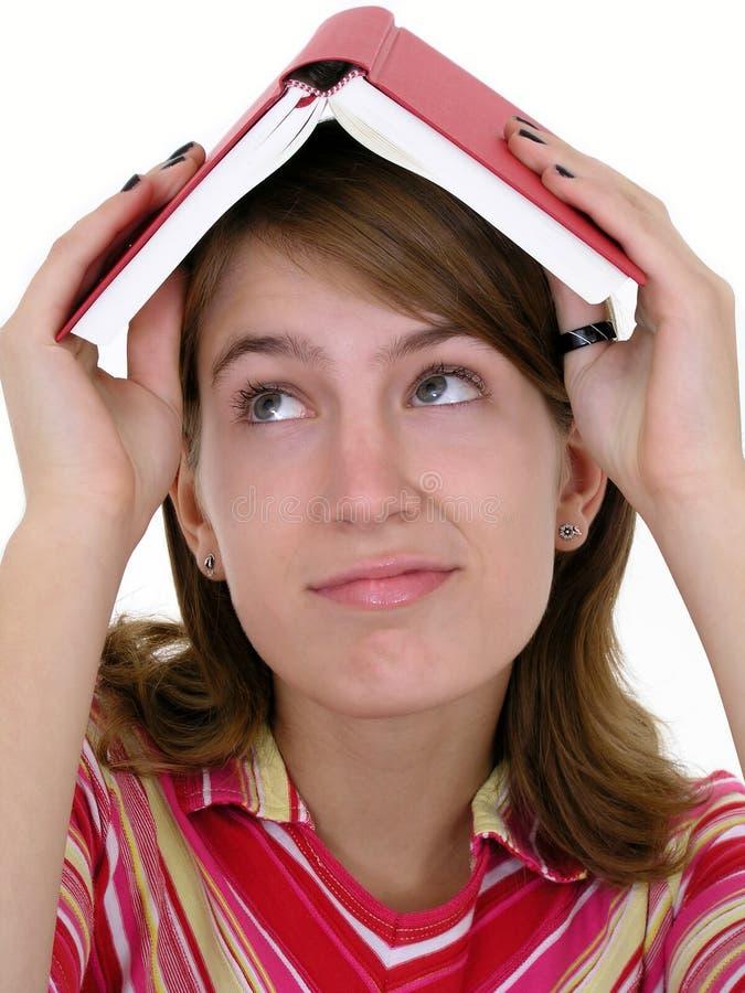 Mädchenholdingbuch auf Kopf stockbilder