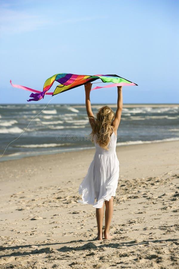 Mädchenholdingdrachen auf Strand. lizenzfreie stockfotos