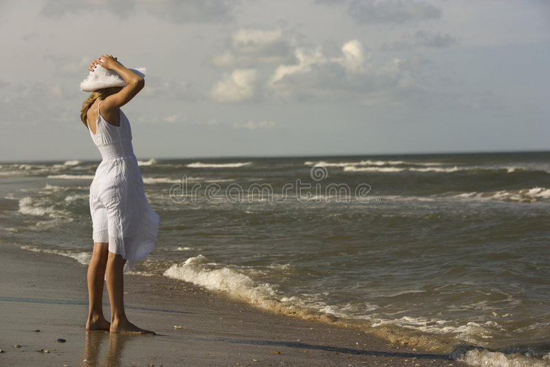 Mädchenholdinghut auf Kopf am Strand. lizenzfreie stockfotos