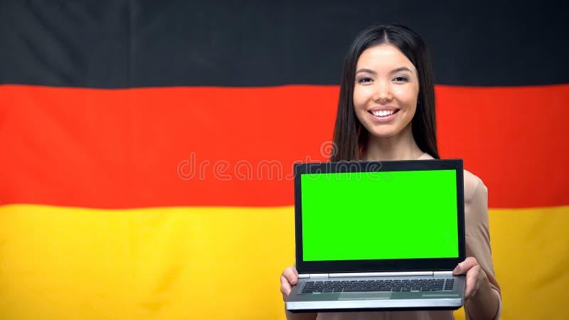 Mädchenholdinglaptop mit grünem Schirm, deutsche Flagge auf dem Hintergrund, reisend lizenzfreie stockfotos