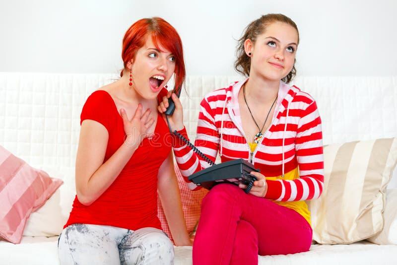 Mädchenholdingtelefon am Ohr ihre überraschte Freundin stockfoto