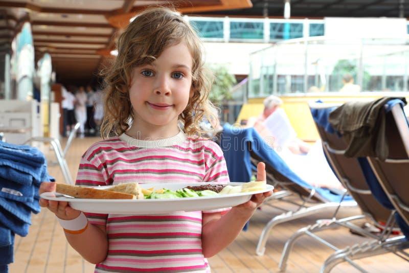 Mädchenholdingtellersegment mit Nahrung auf Reiseflugzwischenlage lizenzfreie stockbilder