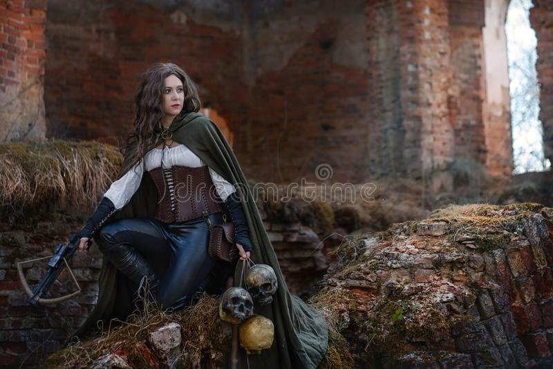 Mädchenjäger mit einer Armbrust auf den Ruinen stockfoto
