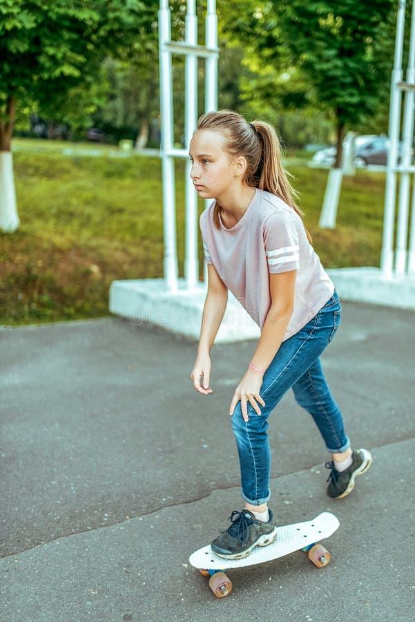 Mädchenjugendlicher 10-15 Jahre alt, ein Skateboard reiten Im Sommer in der Stadt in den zufälligen Jeans und in den Turnschuhen  lizenzfreies stockfoto