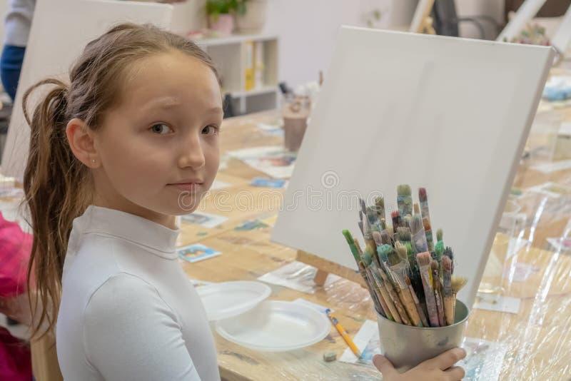 Mädchenjugendlicher 9 Jahre alte Sitzen an einem Tisch vor dem Gestell und Betrachten der Kamera Kreativit?t und Leutekonzept stockfotografie