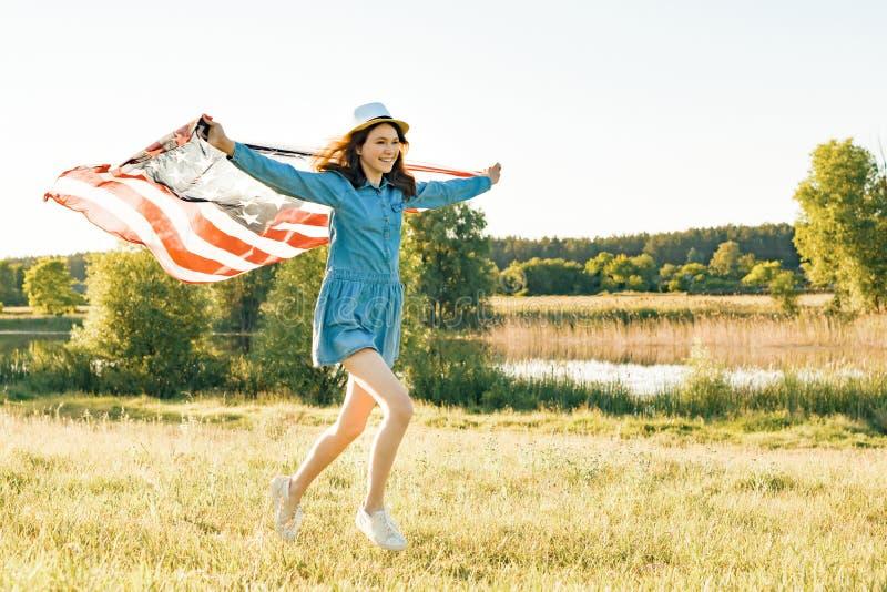 Mädchenjugendlicher mit der amerikanischen Flagge, die durch die Sommergrünwiese bei Sonnenuntergang läuft Naturhintergrund, länd stockfotos