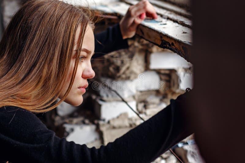 Mädchenjugendlicher schaut aus dem bombardierten und defekten Gebäude heraus zur Straße stockbild