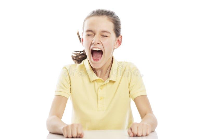 Mädchenjugendlicher Schreien eines in den gelben Hemdes, die am Tisch sitzen Getrennt auf einem wei?en Hintergrund stockfoto