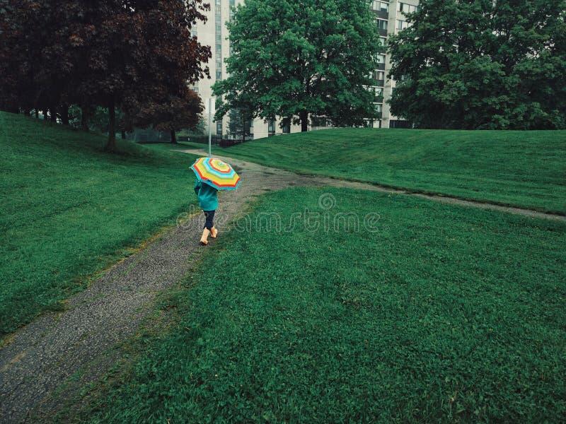Mädchenkind, das auf Straßenstraße unter Regen mit Regenbogenregenschirm geht stockbilder