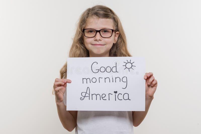 Mädchenkind, das Blatt Papier mit Wort GOOD MORNING AMERIKA hält Weißes bakgrounde stockfotografie