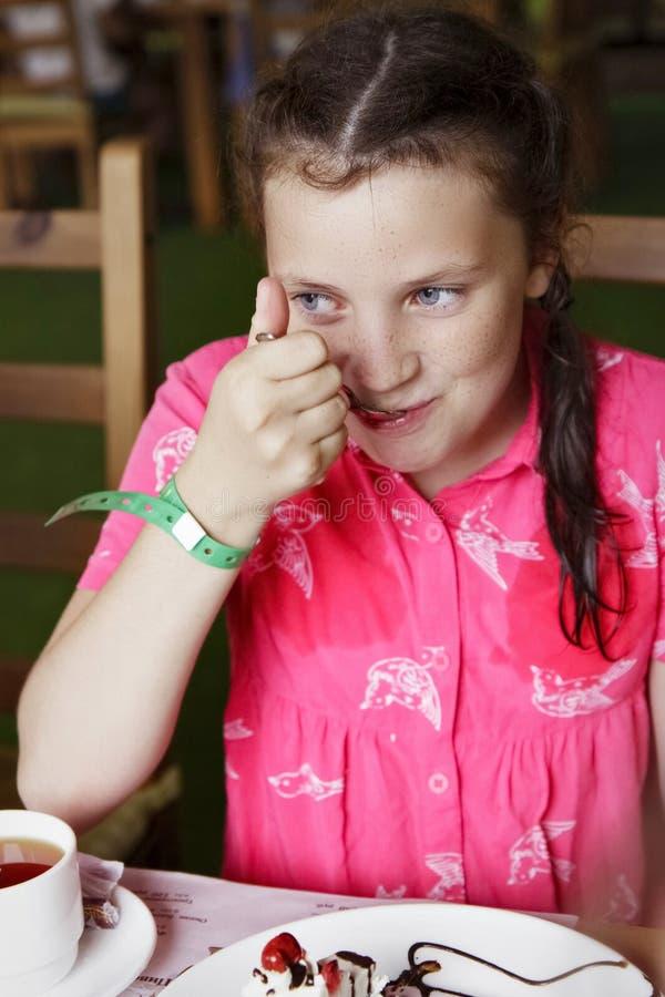 Mädchenkind, das Kuchen im Café isst stockfotos