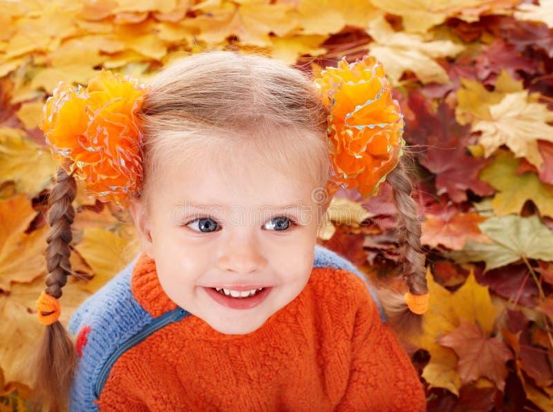 Mädchenkind in den orange Blättern des Herbstes. stockbilder